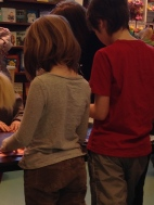 Thing 2 & Thing 1 engaged in a KLUTZ cootie catcher and paper airplane tutorial at Chapters.