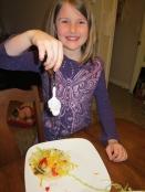 Thing 2 adding some Greek yogurt to her soft flour tortilla taco.