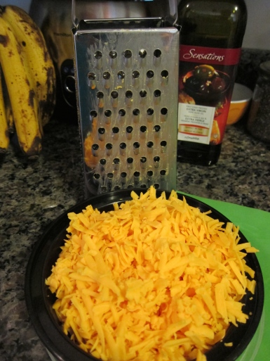 "Yummy! Shredded cheese. At this point little hands start arriving to ""test"" the goods."