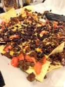 """Restaurant style tortilla chips, three cheese """"shreddar"""", another layer of tortilla chips, bit of cheese, browned ground beef, Tex-Mex seasoning, red pepper dice, tomato dice, black beans. 350 oven until melty, crispy and delicious."""